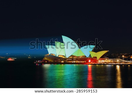 SYDNEY, AUSTRALIA - JUNE 2, 2013;  Sydney Opera house with lovely light gren, aqua and yellow roof sails, during Vivid Sydney.  8 second exposure. - stock photo
