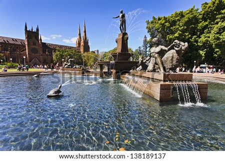 Sydney Australia landmark hyde park day time archibald fountain water sunny reflection trees and cathedral - stock photo