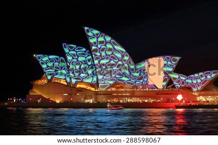 SYDNEY, AUSTRALIA - MAY 23, 2015;  Hand grabbing pattern on Sydney Opera House, one of the many fast moving designs projected onto the iconic building for Vivid Sydney. High ISO - stock photo