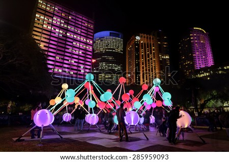 SYDNEY, AUSTRALIA, MAY 27, 2015:  Tourists and public enjoy the Affinity installation at Vivid Sydney, which depict the  human brain and neurons.  When touched, the orbs display sound and light.   - stock photo
