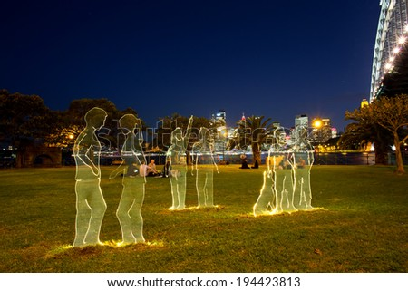 SYDNEY,AUSTRALIA - May 23,2014: Young adults enjoy an exhibit next to the Harbour Bridge on the first night of Vivid 2014. Vivid is a major annual festival of projections and light installations. - stock photo