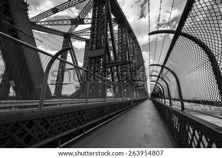 SYDNEY, AUSTRALIA - NOVEMBER 23, 2014: Black and white image of the view of the pedestrian walkway on the famous Sydney Harbour Bridge in November 2014. - stock photo