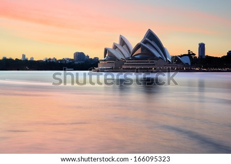 SYDNEY, AUSTRALIA - NOVEMBER 28, 2013; Iconic landmark, the Sydney Opera House and Sydney Harbour and foreshore at sunrise, before most harbour traffic stirs the waters.  Long exposure. - stock photo