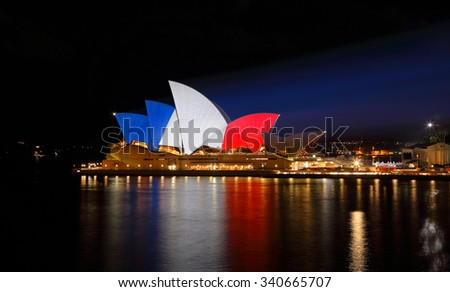 SYDNEY, AUSTRALIA - NOVEMBER 16, 2015;  Sydney Opera House lit up in colours of  French flag blue, white and red in support of tragic terrorist events in France  by  islamic extremist group named ISIS - stock photo