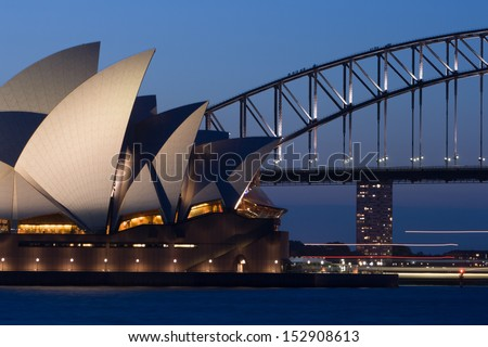 Sydney, Australia - October 21 - The sun sets behind Sydney Opera House and Sydney Harbour Bridge on October 21st 2007. - stock photo