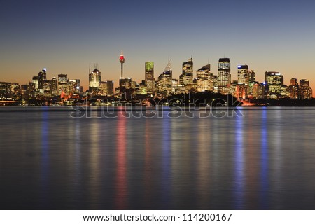 Sydney cbd cityscape at sunset with illuminated lights reflected in sydney harbour waters - stock photo