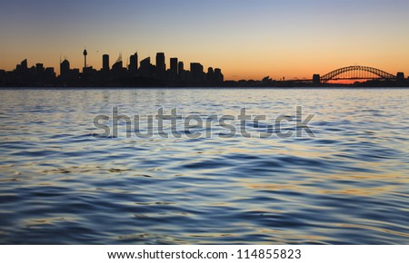 sydney city australia panoramic silhouette view on CBD and harbour bridge with harbour water at sunset - stock photo