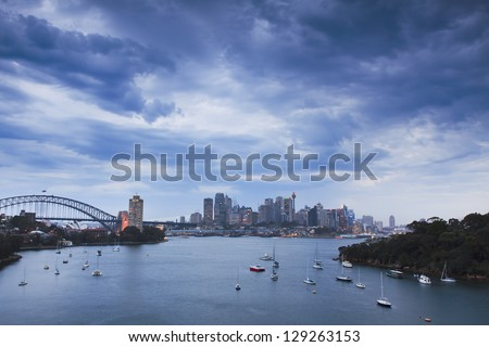 sydney city cbd and harbour bridge at thunderstorm weather with heavy clouds over harbour water with boats at sunset - stock photo