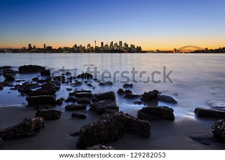 sydney city CBD and harbour view from bradley head reserve park around harbor at sunset with rocks in sea water on foreground panoramic cityscape - stock photo