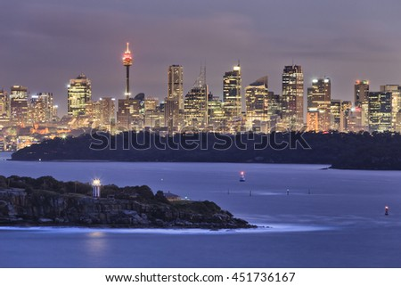 Sydney city CBD towers and office skyscrapers seen from long distance of North Head  entrance to Sydney harbour. South head lighthouse navigating at sunset. - stock photo