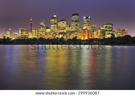 Sydney city line reflecting in blurred still waters of harbour cove at sunset casting colourful shades from illuminating lights - stock photo