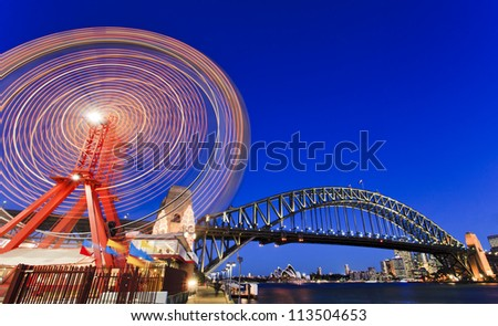 sydney city luna park wheel with harbour bridge arch at sunset illuminated lights and blurred motion - stock photo