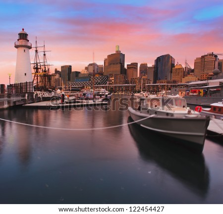 sydney darling harbour maritime museum lighthouse and boats at sunset blurred surrounded by city skyscrapers cloudy red sky and still bay water - stock photo