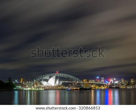SYDNEY - DECEMBER 27 2013 Sydney Skyline, Sydney harbour bridge, Sydney Opera House at night under storm with blue sky blur cloud and Reflection circular quay from Mrs Macquarie's Chair, Australia  - stock photo