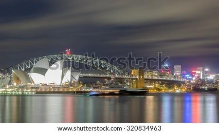 SYDNEY - DECEMBER 27 2013 Sydney Skyline, Sydney harbour bridge, Sydney Opera House at night with blue sky blur cloud long exposure and Reflection circular quay from Mrs Macquarie's Chair, Australia  - stock photo