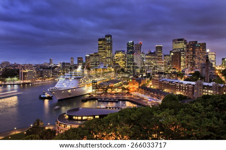 sydney harbour and city CBD at sunset with ocean liner at overseas terminal illuminated with lights - stock photo