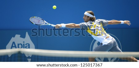 SYDNEY - JAN 9: Feliciano Lopez from Spain stretches for a backhand at the APIA Sydney Tennis International. Sydney January 9, 2013. - stock photo
