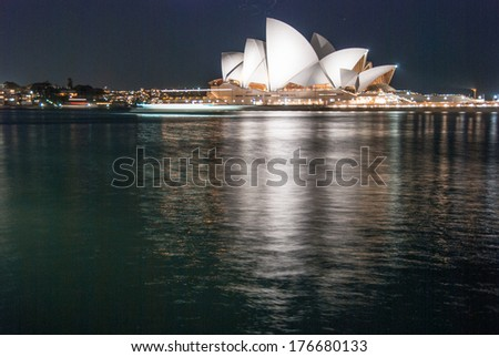 SYDNEY - JUL 22, 2010: Sydney Opera House at night with water reflections. The Iconic Sydney Opera House is a multi-venue performing arts centre also containing bars and outdoor restaurants. - stock photo