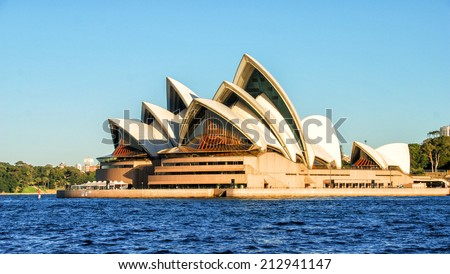 SYDNEY - JULY 21, 2010: Opera House with city vegetation on background. The Sydney Opera House is a famous arts center. It was designed by Danish architect Jorn Utzon, finally opening in 1973 - stock photo