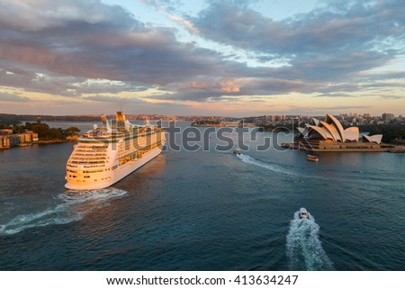 SYDNEY - MARCH 31: Large ocean liner unfolds in Sydney Harbour. View from the Harbour Bridge at sunset. March 31, 2016 in Sydney, Australia. - stock photo