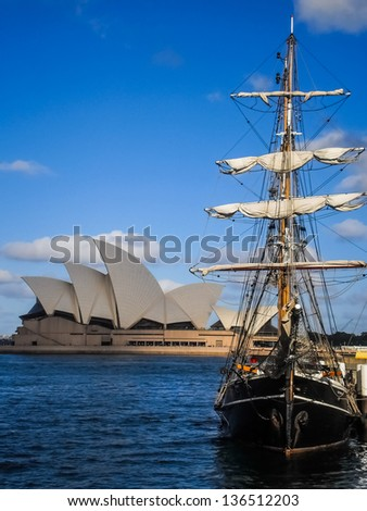SYDNEY-OCTOBER 31:Sailing boat stop at Sydney Harbour with Sydney opera house background ,October 31,2011 in Sydney Australia.Sailing boat service for a group of tourist . - stock photo
