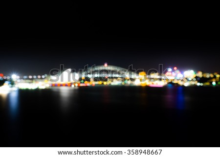 Sydney Opera House And Harbor Bridge at night in blurred background with colorful bokeh - stock photo