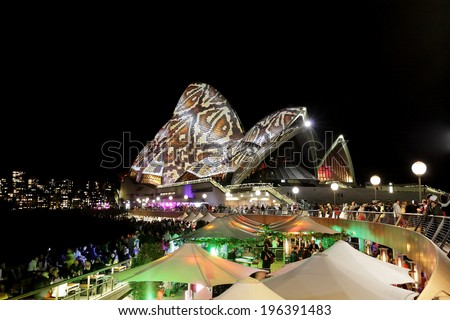 SYDNEY OPERA HOUSE, AUSTRALIA - MAY 28, 2014 -  Reptile snake skin print light up the Sydney Opera House sails during Sydney Vivid Festival.  Crowds of locals and tourists on the foreshore.   - stock photo