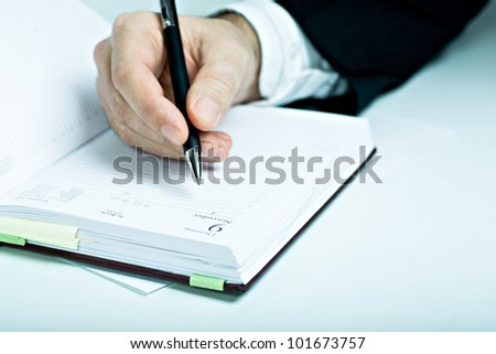Symbilic picture. Suited man with schedule book. - stock photo
