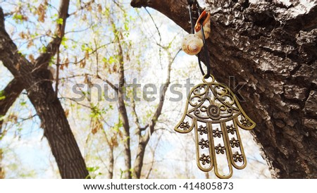 symbol hamsa or hand of Fatima hanging on a tree branch on a background of trees - stock photo