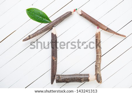 Symbol of a house made up of wooden pencils and green leaf - stock photo