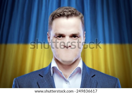 Symbol of censorship and freedom of speech: a young man without a mouth on a background of the national flag of Ukraine - stock photo
