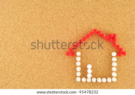 Symbol of home, pinned on cork board - stock photo