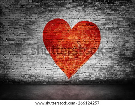 Symbol of love painted on murky, sullen brick wall - stock photo