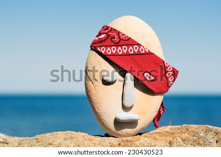 Symbol of stone head  with a patterned red bandana  - stock photo