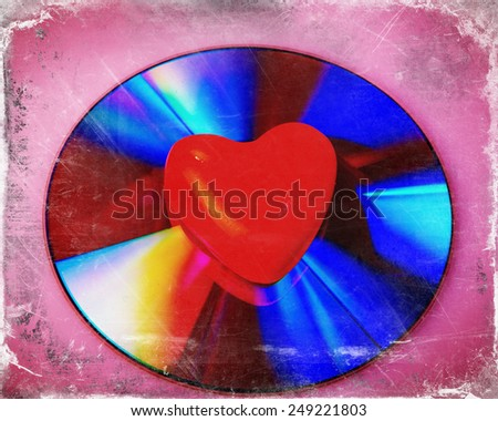 symbol of valentine heart lies on a DVD disc - stock photo
