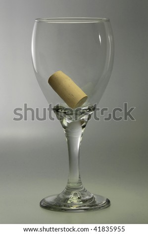 Symbolic empty wine glass containing the bottle cork - stock photo