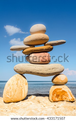 Symbolic figurine of inukshuk of the pebbles on sea background - stock photo