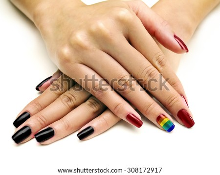 Symbolic LGBTQ pride rainbow nail art manicure on females holding hands.  The hands are on a white background.  The pinkie manicure is multiple colors. - stock photo