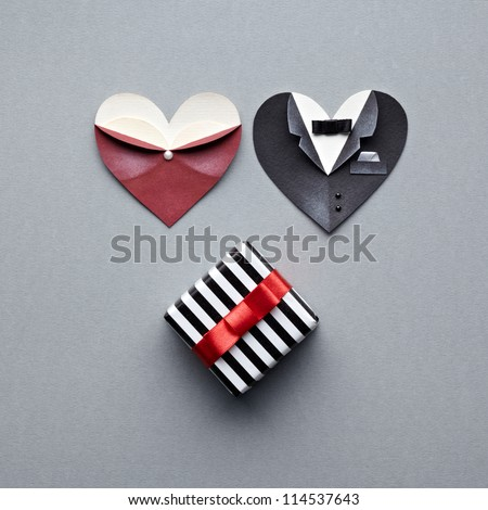 Symbolic male and female heart shapes with gift box. On gray background. Wedding or st.Valentine theme. - stock photo