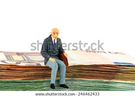 symbolic photo for retirement and old age, figure of an old man sitting on a stack of bills - stock photo