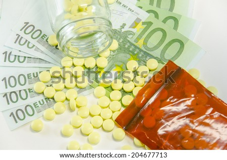 Symbolic picture for high cost of medicine with pills on money - stock photo