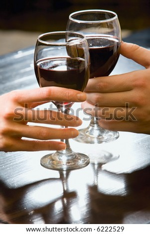 Symbolic picture of glasses of red wine in human hands - stock photo