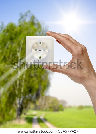 symbolic solar energy theme showing a idyllic outdoor scenery with human hand holding a electrical socket in front of the sun while sunbeams falling through - stock photo