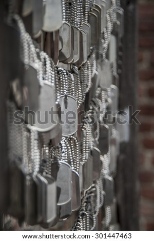 Symbolically blank soldier dog tags  at a memorial - stock photo