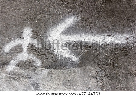 Symbols of person and arrow painted on the wall with white spray paint. - stock photo