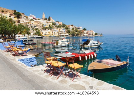 SYMI, GREECE - September 6,2015: Fishing boats moored in Yialos harbour and a beautiful view on a color houses. Symi is easy and most popular destination for day tripping from Rhodes island. - stock photo