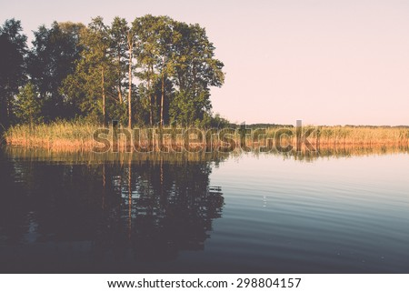 symmetric reflections on calm lake water with forests and islands - retro vintage effect - stock photo