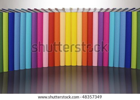Symmetrical curve alignment of in rainbow colors paper wrapped books with blank spine facing front and reflection, view from front-above, PHOTOGRAPH, NOT 3D RENDER. - stock photo