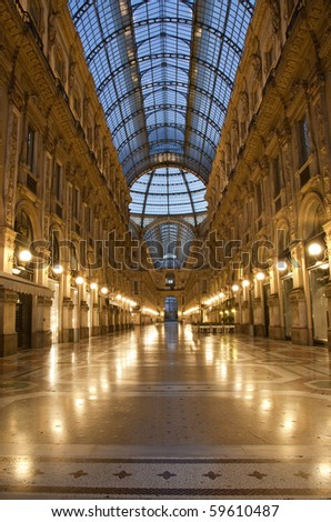 Symmetrical night shot of the hall of the landmark arcade or covered luxury shopping mall, Galleria Vittorio Emanuele II in Milan, Italy, showing the spectacular view of a golden gate to luxury - stock photo