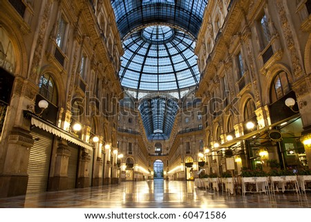Symmetrical night shot of the hall of the landmark arcade or covered luxury shopping mall, Galleria Vittorio Emanuele II in Milan, Italy - stock photo